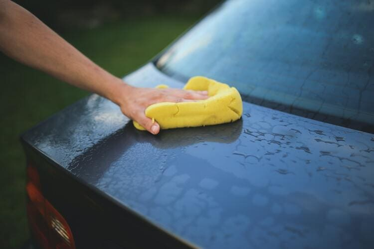 Main qui lave la carrosserie d'une voiture avec une éponge.