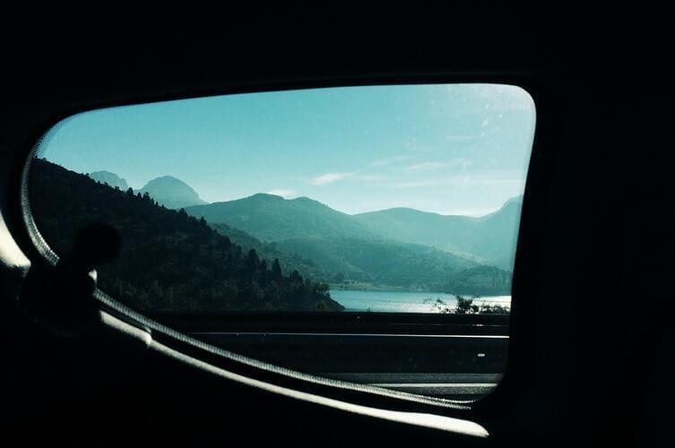 Vue des montagnes à travers un rétroviseur.